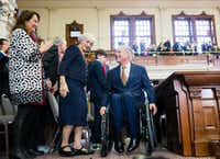 As Texas first lady Cecilia Abbott (left) looked on, Gov. Greg Abbott wheeled himself off the House dais after speaking at the installation of new House Speaker Dennis Bonnen on Tuesday. Bonnen's mother, Matina Bonnen, is at center.(Ashley Landis/Staff Photographer)