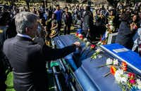 "Austin Mayor Steve Adler places a flower on Overton's casket. ""It was impossible to be around that man, who was gentle and respectful and kind, and not be gentle and respectful and kind in return,"" Adler said.(Ashley Landis/Staff Photographer)"