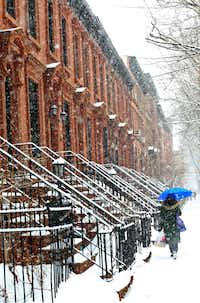 A woman carries an umbrella on a snowy day in Brooklyn. Be careful: One strong gust of winter wind is all it takes to destroy your umbrella.(2015 File Photo/Getty Images)