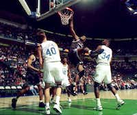 Shaquille O'Neal of the Orlando  Magic, attempts a slam dunk in the first period aganist the Dallas Mavericks at Reunion arena Thursday, March 3, 1994 in Dallas. #40, Greg Dreiling, of Dallas and #34, Doug Smith, look on.(David Woo/The Dallas Morning News)
