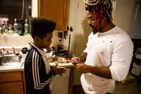 Dorelle Harrison teaches his son, Prince Harrison, how to use chopsticks in his Dallas home on Jan. 15, 2019. Harrison works for the Environmental Protection Agency as a physical scientist. Due to the government shutdown, Harrison was furloughed and has not been working.(Shaban Athuman/Staff Photographer)