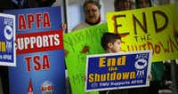 Airport employees and their families protest the government shutdown on Jan. 16 outside of Terminal D at Dallas-Fort Worth International Airport.(Tom Fox/Staff Photographer)