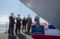 Georgeann McRaven christens the USS Ralph Johnson, a guided missile  destroyer, on her first blow to the bow on April 2, 2016.(Huntington Ingalis Industries)