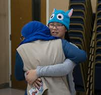 Girl Scout Cadettes Sophia Laska (right) of Troop 882, and Redda Hassen, Troop 647, hug before their combined meeting at the Islamic Association of North Texas mosque in Richardson. They were former classmates who were reunited at the meeting.(Daniel Carde/Staff Photographer)