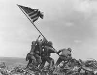 "The book includes some iconic photos, such as Joe Rosenthal's ""Raising the Flag on Iwo Jima,"" while also devoting space to relatively unknown photographs.  (The Associated Press/1945 File Photo)"