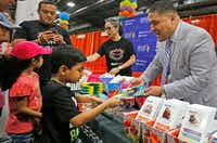 Dallas school board member Jaime Resendez hands out items to parents and students at the Bilingual ESL/Dual Language Programs  booth at the Dallas Mayor's Back to School Fair held at the Centennial Building at Fair Park in Dallas on Aug. 3, 2018. (Louis DeLuca/Staff Photographer)