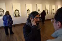 Peruvian artist Rudolph Castro (center) speaks with a visitor to his art exhibition at the Oak Cliff Cultural Center. The exhibit tells the stories of families who were victims of military regimes in Latin America.(Ben Torres/Special Contributor)