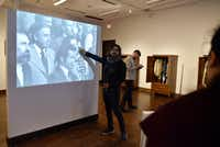Peruvian artist Rudolph Castro speaks about a video projected on a wall at his exhibition at the Oak Cliff Cultural Center. His trip to Dallas was his first visit to the United States. (Ben Torres/Special Contributor)