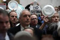 "Federal employees hold up signs made with Styrofoam plates during a protest at the atrium of Senate Hart Office Building in Washington, D.C., on Jan. 23, 2019. Federal employees from different unions participated in an ""Occupy Hart"" protest on Capitol Hill against the partial government shutdown. (Alex Wong/Getty Images)"