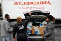 TSA employee Princess Young, center, loads food into a car after visiting a food pantry for furloughed government workers affected by the federal shutdown, Wednesday, Jan. 23, 2019, in Baltimore. (Patrick Semansky/AP)