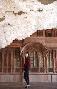Evelyn Chun looks up at Jacob Hashimoto's installation <i>Nuvole </i>against the Facade of a Residence at the Crow Museum of Asian Art in Dallas on Jan. 24, 2019.(Rose Baca/Staff Photographer)