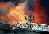 A Dallas firefighter gestures when the water pressure dropped suddenly while battling a six-alarm blaze at an the historic Crozier Tech High School in downtown Dallas Monday, April 19, 1999.(FREILICH, Jon/The Dallas Morning News)