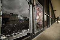Broken glass and outdated casino posters are visible on the vacated storefront of 12125 Abrams Road, Suite 111. (Tom Fox/Staff Photographer)