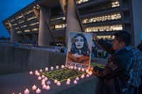 Luis Gonzalez, a DACA recipient originally from Mexico, places candles around a protest sign before a vigil at Dallas City Hall on March 5, 2018.(Rex C. Curry/Special Contributor)