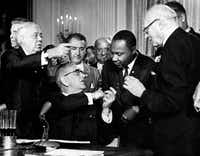 President Lyndon B. Johnson hands a pen to the civil rights leader the Rev. Martin Luther King after signing the historic Civil Rights Act in the East Room of the White House, in Washington, D.C., July 2, 964. (Agence France-Presse)