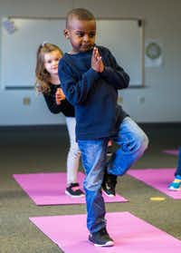 Joshua Oatis and other kindergarteners work on balance and other yoga principles during a yoga class at Pink Elementary School in Frisco ISD.(Ashley Landis/Staff Photographer)