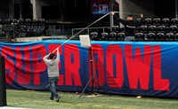 Workers use a tape measure as they hang a sign Jan. 29 inside Mercedes-Benz Stadium for Super Bowl 53 in Atlanta. (David J. Phillip/The Associated Press)