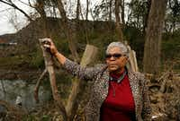 Homeowner Marsha Jackson stands alongside the flood-damaged fencing bordering a large hill of recycled roof shingles (in background) near State Highway 310 and Interstate 20 in southern Dallas.(Tom Fox/Staff Photographer)