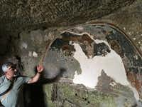 Tonio Creanza, founder and director of Messors, gestures near a fresco in the crypt of Carpentino in Altamura, Italy. The underground church was dug out of soft limestone.(Ben Yagoda/The Washington Post)