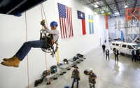 FCC commissioner Brendan Carr did a controlled descent while touring Swedish telecom company Ericsson's tower training facility in Lewisville. He also participated in a ribbon cutting for the center.(Tom Fox/Staff Photographer)