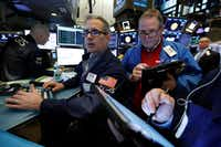 Specialist Anthony Rinaldi, left, and trader Michael Conlon worked on the floor of the New York Stock Exchange on Tuesday.(Richard Drew/The Associated Press<br>)