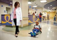 Dr. Tiffany Simms-Waldrip (left) walks the halls of the Stem Cell Transplant Unit with patient Akshaj Nagilla, who uses an exercise roller, at Children's Medical Center Dallas on Jan. 15, 2019. Akshaj, 7, just received a second transplant to treat his leukemia. Simms-Waldrip is a associate professor of pediatrics at UT Southwestern Medical Center and clinical director of the marrow transplant program at Children's Health. (Tom Fox/Staff Photographer)