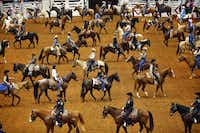 Stock Show officials, dignitaries, and participants on horseback form a serpentine line during the Grand Entry on Feb. 1 at Will Rogers Memorial Coliseum. The procession, which kicks off the Stock Show's PRCA rodeo, is a longtime tradition of the rodeo, dating back to the beginning in 1918.(Tom Fox/Staff Photographer)