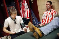 In the Justin Sportsmedicine room, bullfighter Nathan Harp of Tuttle, Oklahoma (left) wraps a brace around his arm as he prepares to go face-to-face with bulls during the PRCA rodeo riding event at the Will Rogers Memorial Coliseum, Saturday, February 2, 2019. Three-time world champion bullfighter Evan Allard (right) of Vinita, Oklahoma has been doing this full time for the past 14 years.(Tom Fox/Staff Photographer)