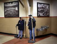 A pair of custodians visit along the historic, photo-lined walls of Will Rogers Memorial Coliseum, Thursday, January 31, 2019.(Tom Fox/Staff Photographer)