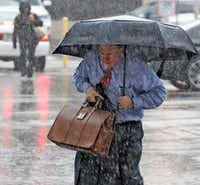 A man made his way through a downpour as he arrived at the Earle Cabell federal courthouse in downtown Dallas on Sept. 26, 2018. (File Photo/Staff)