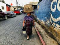 A woman in traditional indigenous dress walks the streets of San Martin Jilotepeque, Guatemala. She confuses a visitor for a smuggler and asks him to leave her alone.(Alfredo Corchado/Staff)