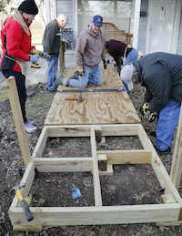 Project manager Kirk Saxon (center) of Melissa, Texas surveys the situation from his knees as The Kiwanis Club of McKinney builds a wheelchair ramp at the home of Rachel Armijo, in McKinney on Saturday morning, January 26, 2019.(Stewart F. House/Special Contributor)