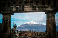 The snow-covered peak of Mount Vesuvius is framed by ancient ruins of the archaeological excavations of Pompeii. Guests of the art restoration program took an overnight trip to Pompeii and Naples.(Cesare Abbate/The Associated Press)