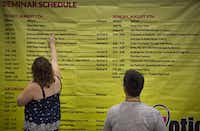 "Shelly Burroughs of Princeton, Texas, looks over a schedule during the since ousted Exxxotica Expo held at the Kay Bailey Hutchison Convention Center. Under the management agreement, ""certain events"" would need city approval.<br>(Staff photographer/G..J. McCarthy)"