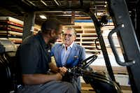 Wayne Gono, visionary/chief networking officer of Regal Plastics, talks to employee Vernon Mason. The Irving fabrication business uses wearable fitness trackers to help employees be healthier.(Allison V. Smith/For The Washington Post)