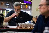Jasper Russo, (left) director of wine marketing at Sigel's Fine Wines & Great Spirits, pairs a red wine with samples of boudin during a boudin and wine tasting.(Ashley Landis/Staff Photographer)