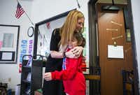Momentous Institute executive director Michelle Kinder hugs fourth grader Rebecca before morning circle time at the Oak Cliff school.(Ashley Landis/Staff Photographer)