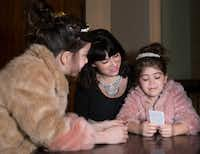 From left, 8-year-old Dotty Rico and her mother, Alicia Rico, talk with Dotty's sister, 5-year-old Pia Rico before a performance of <i>Anastasia</i> at the Music Hall at Fair Park in Dallas on Feb. 19, 2019. The Rico sisters were dressed as Anastasia, the lead character from the play. They both wore tiaras they got when they saw the musical in New York City last year.(Daniel Carde/Staff Photographer)