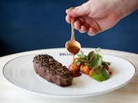 Chef Bruno Davaillon pours sauce on Bison Steak au Poivre.(Rose Baca/Staff Photographer)