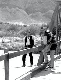 Off-camera and behind-the-scenes, actor William Holden (left) plays daredevil by tightrope-walking a support cable for the bridge that will be blown up in the movie <i>The Wild Bunch</i>.(Paul Harper)