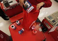 A checker at the Cityplace Target in Dallas loads a customer's purchases into a reusable bag.(2015 File Photo/Staff)