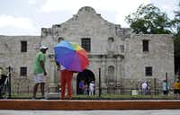 A visitor uses an umbrella to shield the sun during a visit to the Alamo, Monday, June 15, 2015, in San Antonio. The Alamo,  site of the Battle of the Alamo in the Texan War of Independence from Mexico, is one of the most visited historical sites in Texas. (Eric Gay/AP)