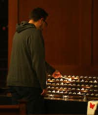 Church member J.J. Heid lights a candle in the sanctuary at Grace Avenue United Methodist Church in Frisco on Wednesday during a prayer service set up after the denomination's anti-LGBTQ vote in St. Louis.(Rose Baca/Staff Photographer)