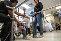 Physical therapist Binu Aramath (left) helps Hareg Wolde's mother as neurologist Dr. Mehari Gebreyohanns and Wolde watch at Parkland Hospital in Dallas.(Carly Geraci/Special Contributor)