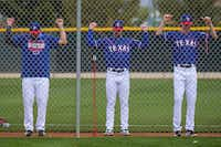 From left: Texas Rangers pitchers Ariel Jurado, Taylor Guerrieri and Luke Farrell stretch using resistance bands at the beginning of their first spring training workout on Feb. 13 in Surprise, Ariz.(Smiley N. Pool/Staff Photographer)
