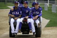 From left: Texas Rangers pitchers Jonathan Hernandez, Adrian Sampson and Nick Gardewine ride a cart back to the clubhouse after throwing a bullpen session during a spring training workout on Feb. 14 in Surprise, Ariz.(Smiley N. Pool/Staff Photographer)
