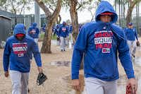 Texas Rangers infielder Ronald Guzman (right) bundles up against a cold rain while walking between practice fields on Feb. 22 at the club's spring training facility in Surprise, Ariz..(Smiley N. Pool/Staff Photographer)
