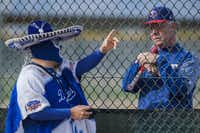 "Los Angeles Dodgers fan Carlos Morales chats with Steve Buechele, Texas Rangers special assistant for baseball operations, on a practice field during a spring training workout on Feb. 25 at the Rangers' facility in Surprise, Ariz.. Morales said he visited the Rangers camp for the day because, ""while the Dodgers are my team, baseball is my sport.""(Smiley N. Pool/Staff Photographer)"