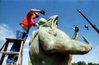 Jerry Hudson of Carl's Corner truck stop does some large-scale frog dissection on one of the landmarks on top of the old Tango nightclub on lower Greenville Avenue in 1985.(1985 File Photo/The Dallas Morning News)