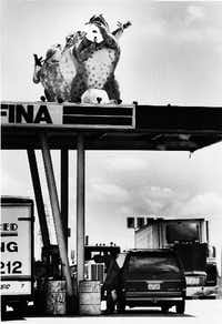 Three of the six Tango Frogs greet motorists as they gas up at Carl's Corner in 1984.  The other three frogs were touring the country.(1984 File Photo/The Dallas Morning News)